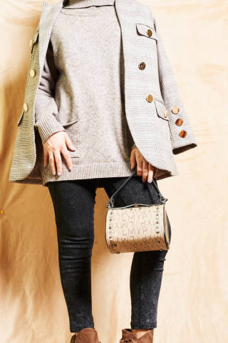 An unrecognizable model wearing a casual outfit holding handbag