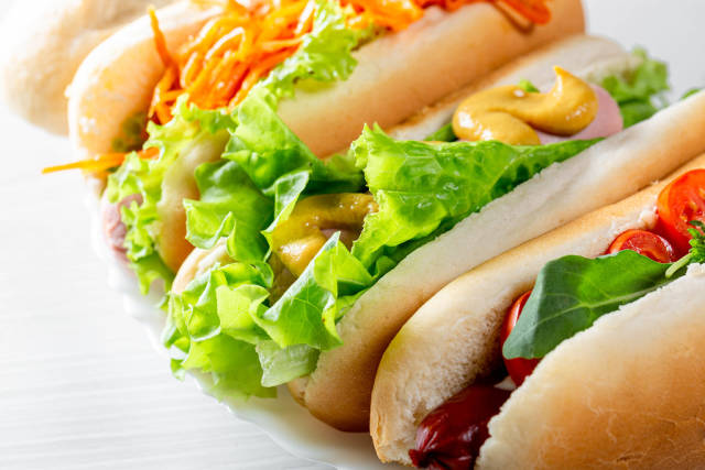 Three fresh hot dogs with vegetables, sausages and greens close-up