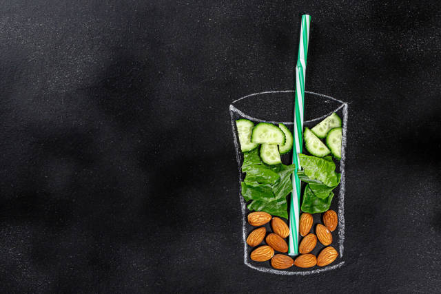 Food ingredients for blending smoothie -cucumbers, lettuce, almonds in painted glass on black chalkboard. Top view with copy space