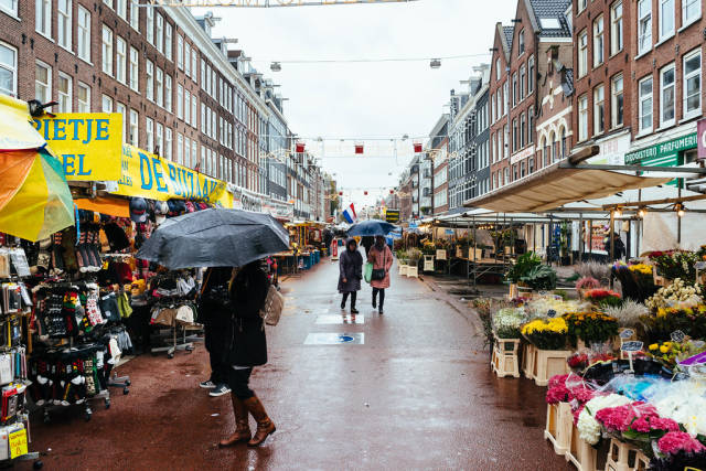 Tourists walking in the rain at Albert Cuyp street market in the city of Amsterdam