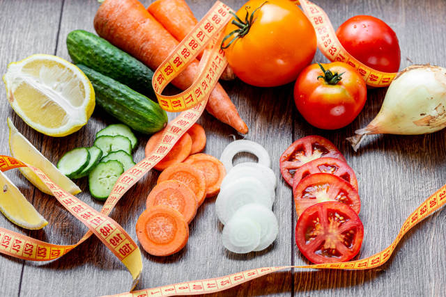 Fresh vegetables with measuring tape on the table. Healthy eating concept (Flip 2019)