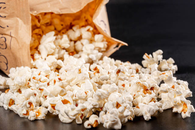 Homemade fresh popcorn with paper package on black