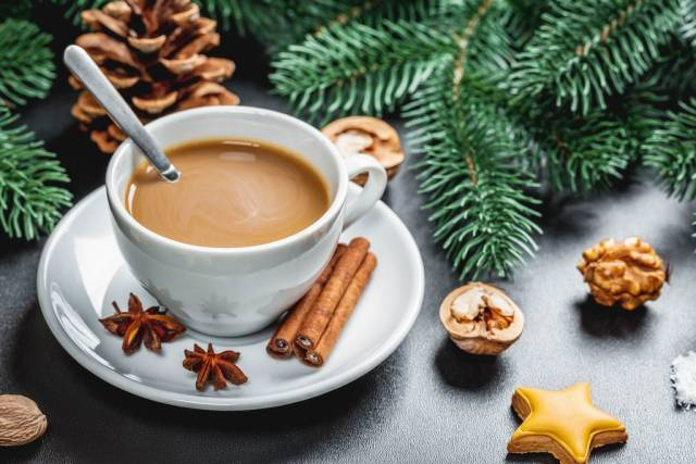 Eine Tasse Kaffee mit Zimt Walnüssen und Tannenzweigen