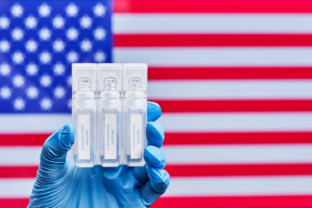 Doctor holds three doses of Covid-19 vaccines against American flag
