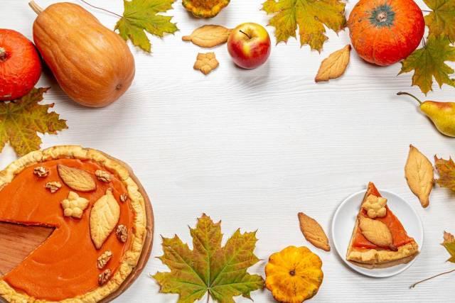 Herbst Rahmen mit Blättern, Kürbiskuchen, Äpfeln, reifen Kürbissen und hausgemachten Keksen auf weißem Holzhintergrund