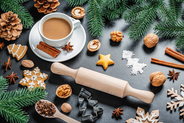 Coffee with anise and cinnamon on a New Years background with a rolling pin, Christmas tree branches, gingerbread and cones