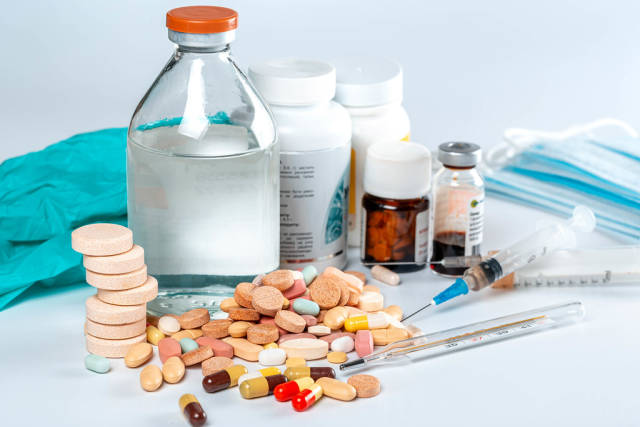 Medicines background with multicolored pills and medicine bottles