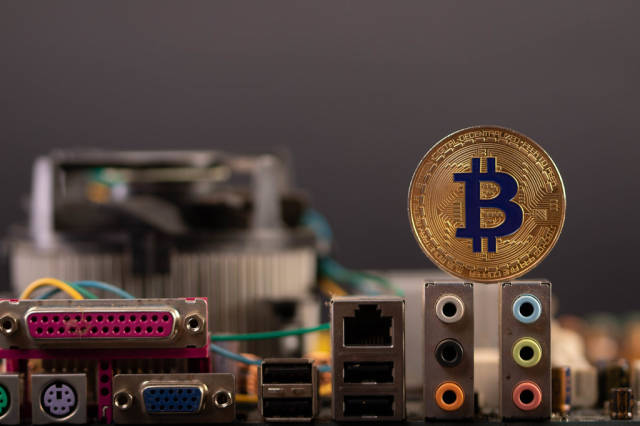 Golden Bitcoin with computer parts