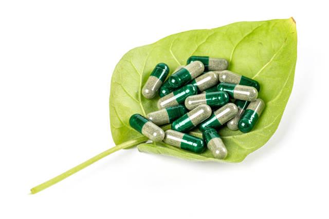 Herbal medicine capsules on green leaf