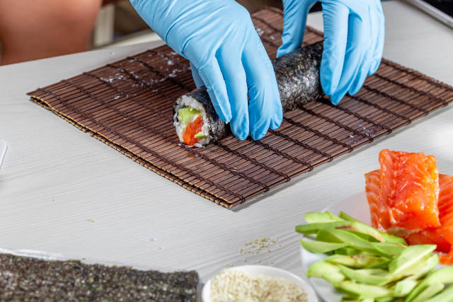 Chef hands in disposable gloves cooking sushi at kitchen of home