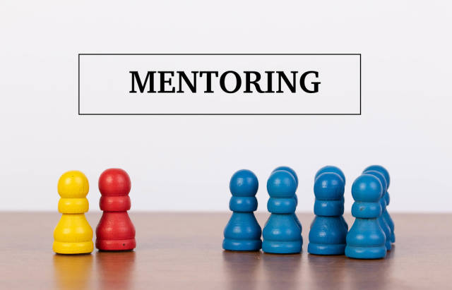 Mentoring concept with pawn figurines on table