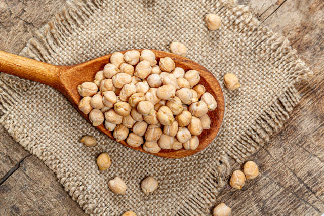 Chickpeas in a wooden spoon on burlap. Top view