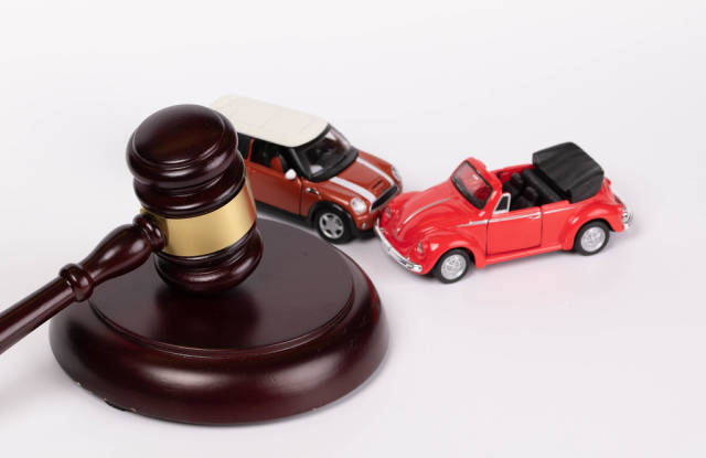 Gavel and two toy cars on white background