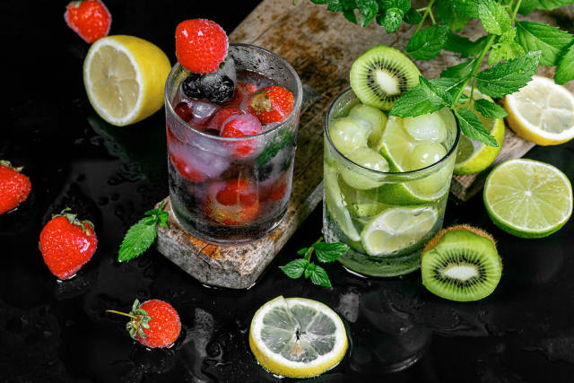 Summer fruit cocktails with ice, berries and mint