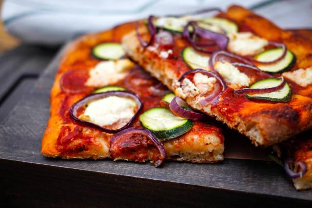 Vegetarische Pizza mit Zucchini und roten Zwiebeln