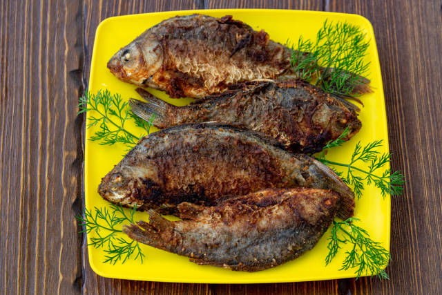 Fried crucian fish on a wooden table