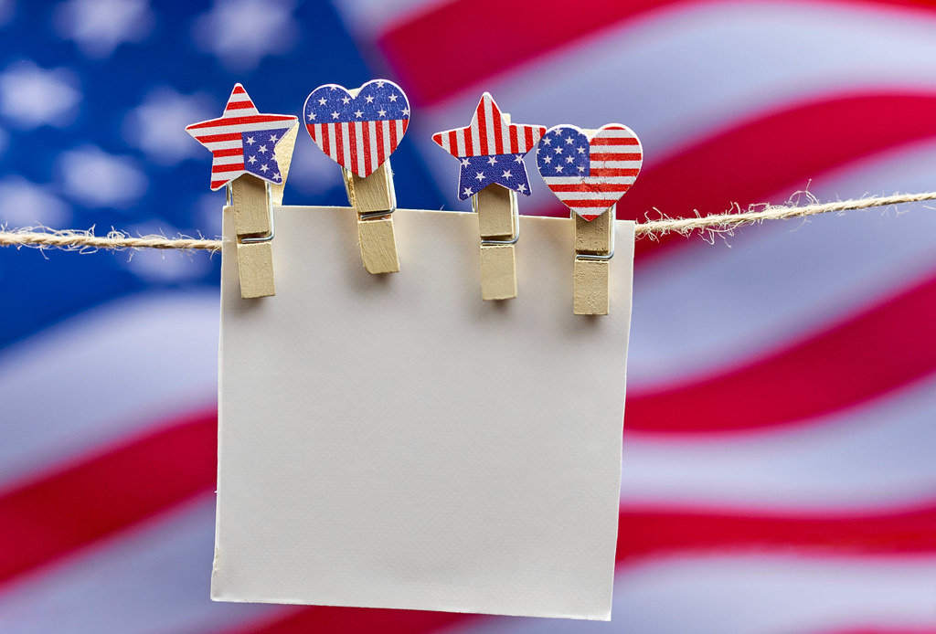 A piece of blank card hanging on the rope with american flag on the background