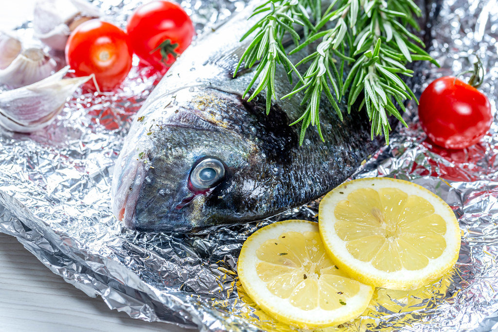 Close - up Dorado fish with rosemary, lemon slices and tomatoes on foil