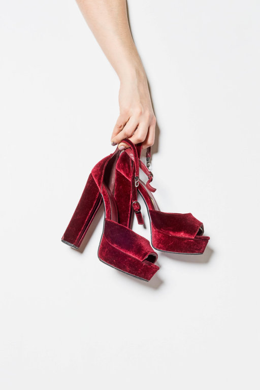A girl picked up trendy red high hill shoes
