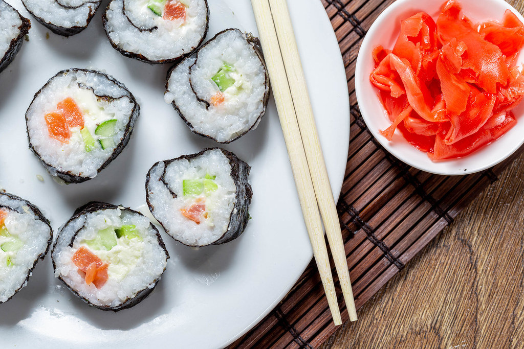 A plate of Maki rolls, chopsticks and ginger