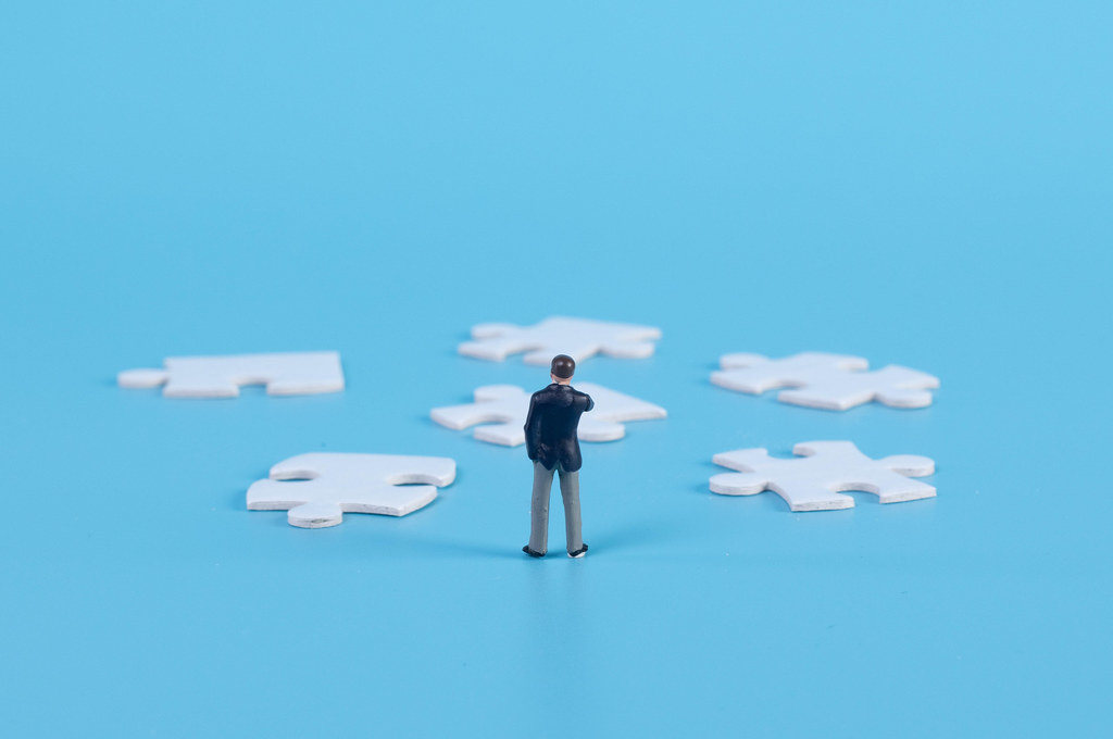 A miniature businessman standing with a puzzle pieces