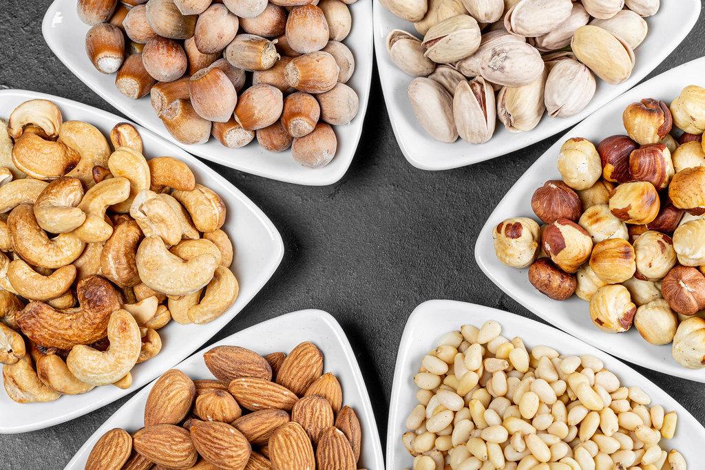 Almonds, hazelnuts, pine nuts, pistachios, cashews and filbert in triangular bowls