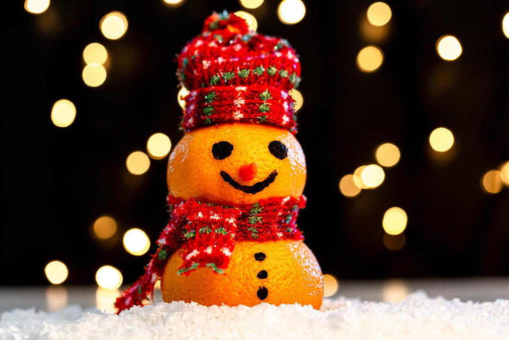 Tangerine snowman in the snow on a blurry background of luminous garlands