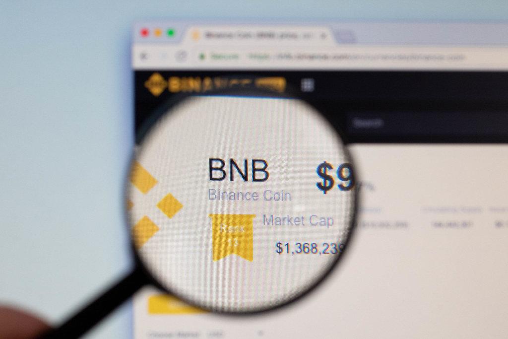 Binance Coin Logo am PC-Monitor, durch eine Lupe fotografiert