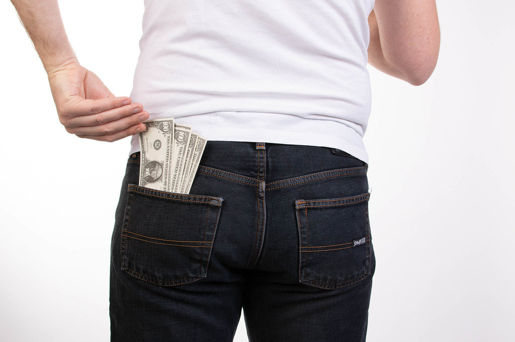 Man pulls the money from his jeans pocket