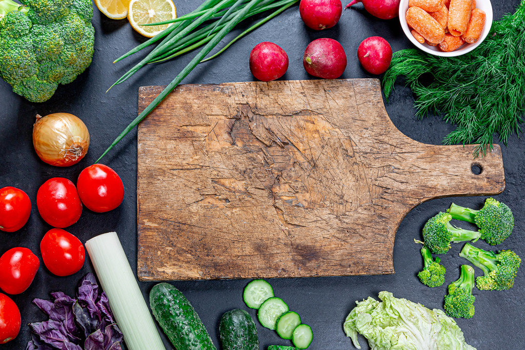 Vegetables and greens frame on a black background and old kitchen Board in the middle