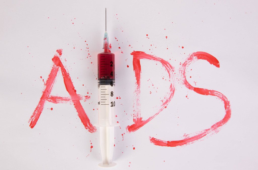Bloody word AIDS with injection needle on white background
