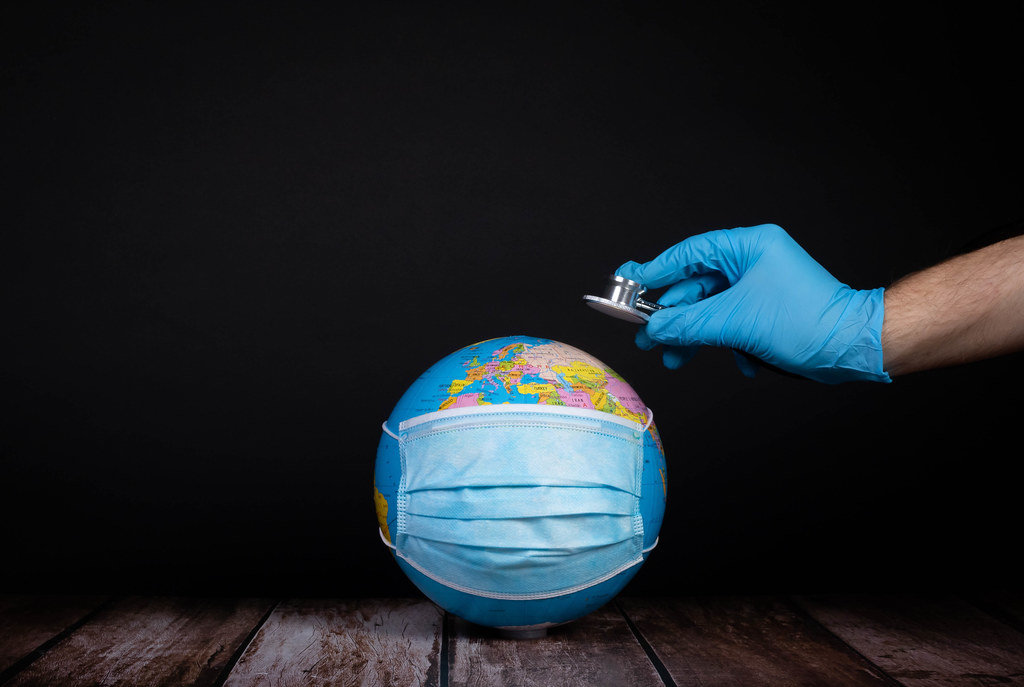 Globe with medical face mask and hand with stethoscope
