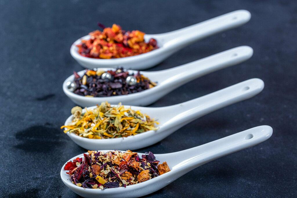 Different varieties of dried tea in ceramic spoons