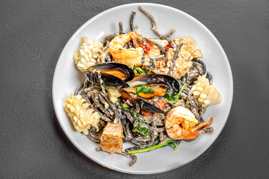 Top view noodles with cuttlefish ink in creamy sauce with seafood