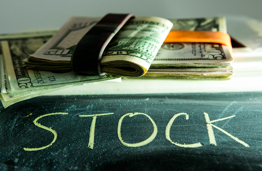 Word STOCK with dollar bills behind