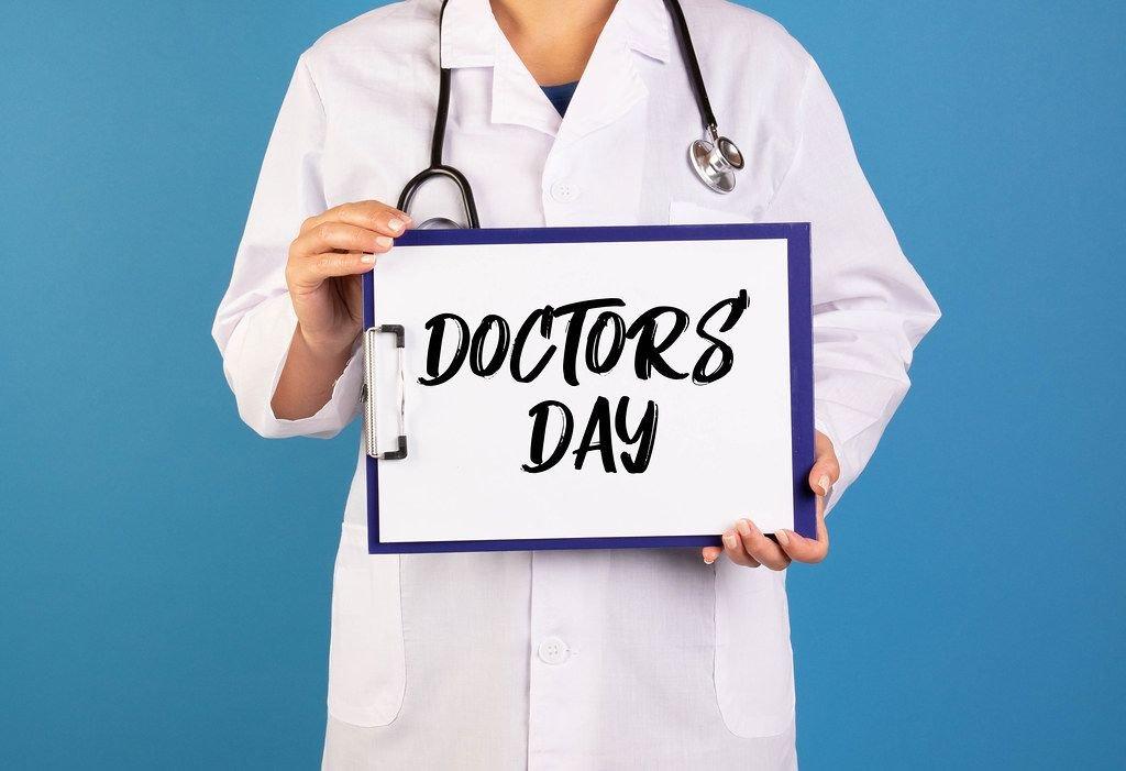 Arzt hält einen Schild mit der Schrift Doctors day im blauen Hintergrund