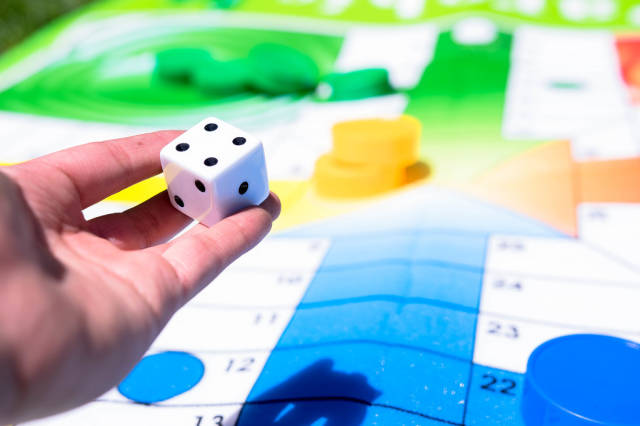 Hand holding dice over giant parchís game mat
