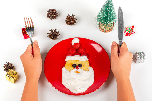 Christmas Santa pancake with berry for kid breakfast on white background and hands with knife and fork