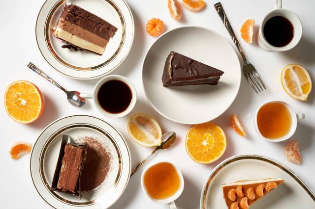 Flatlay: leckere Kaffee- und Teepause mit einem Tortenstück und vielen Zitrusfrüchten