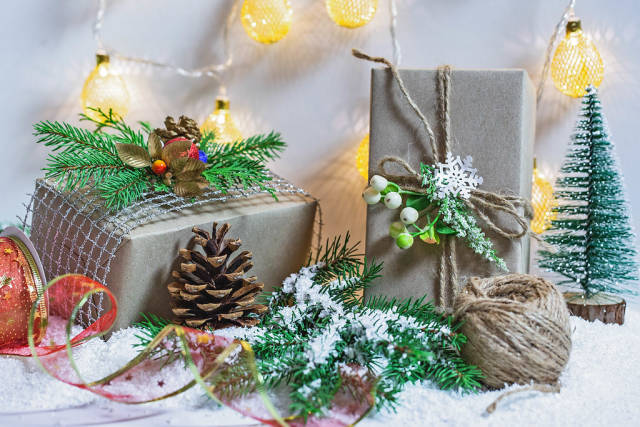 Beautiful decorated gift boxes and New Years décor with a Christmas tree, snow and luminous garland.