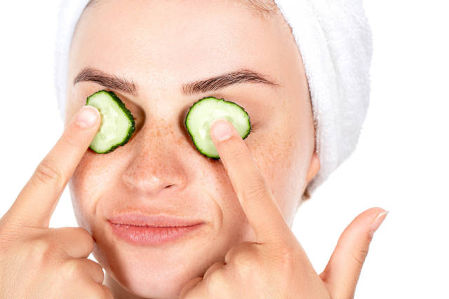 Girl holds fingers slices of cucumber in front of her eyes