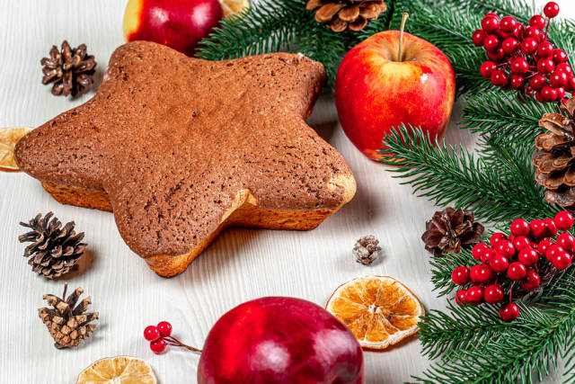 Biscuit in form star on the table with apples, dried citrus and Christmas decor