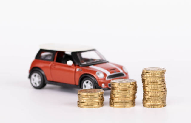Car model and coins on white background