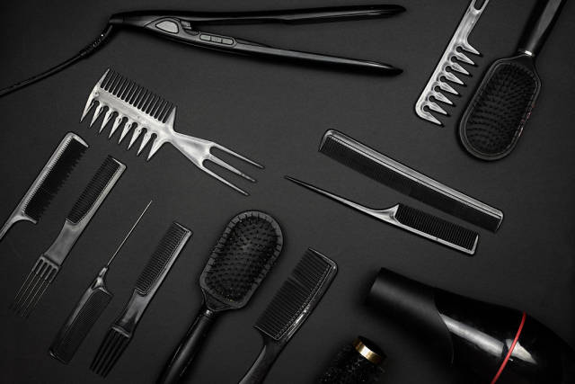 Different hair styling tools on black