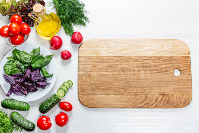 Fresh tomatoes, cucumbers, radishes, greens and lemon and a wooden Board on a white table. The view from the top