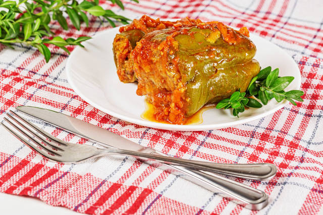 Stuffed bell peppers with tomato sauce on a kitchen towel with a knife and fork