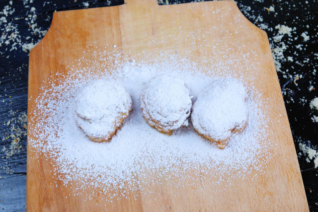 Doughnuts with powdered sugar on wooden background