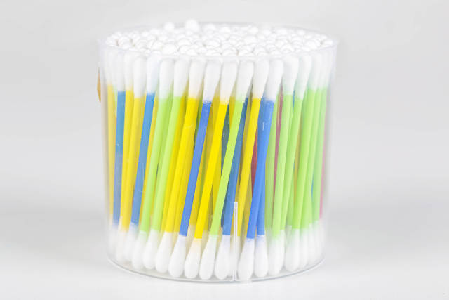Colorful cotton swabs on light background