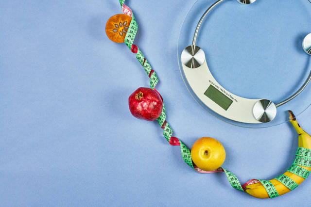 Weight scale and fruits tied with measuring tape