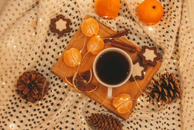 Top view, cup of coffee with cookies, tangerines, garland and pine cones